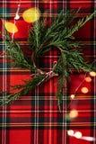 新杉木分支圣诞节花圈在红色方格的织品和出于焦点光 圣诞节概念性背景 免版税图库摄影
