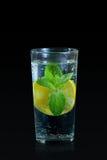 新柠檬饮料用在黑背景的薄菏 免版税图库摄影