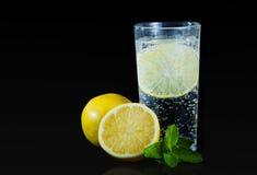 新柠檬饮料用在黑背景的薄菏 免版税库存图片