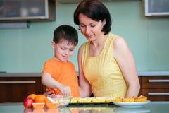新母亲和她小的儿子烘烤松饼 免版税图库摄影