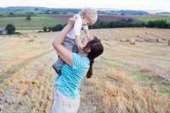 新母亲和她的小儿子获得乐趣在秸杆领域 图库摄影