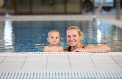 新母亲和她的游泳池的儿子 免版税库存照片