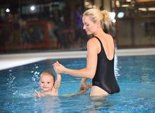 新母亲和她的游泳池的儿子 免版税库存图片