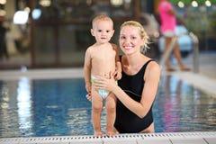 新母亲和游泳池的小儿子 免版税库存照片