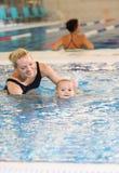 新母亲和游泳池的小儿子 图库摄影