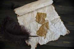 新泽西州地图在葡萄酒纸的与在木纹理书桌上的老笔 库存照片