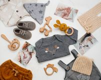 新生儿衣物、木玩具和婴孩照片在白色大理石背景 库存照片