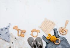 新生儿衣物、鞋子和玩具在轻的大理石背景 免版税库存照片