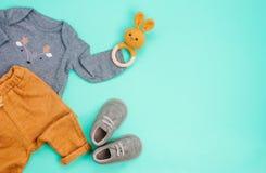 新生儿衣物和兔子装豆子小布袋在绿松石背景 库存图片