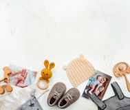 新生儿衣物和玩具om大理石背景 库存图片