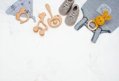 新生儿衣物和装豆子小布袋在大理石背景与拷贝空间 免版税库存图片
