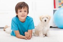 新男孩和他的好正常运行的小狗 免版税库存图片