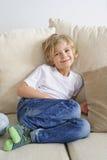 新男孩坐沙发 免版税库存图片