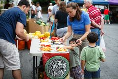 新男孩抽样新鲜水果农夫的市场 库存照片