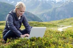 新白肤金发的妇女坐与膝上型计算机在草甸 库存照片