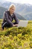 新白肤金发的妇女坐与膝上型计算机在草甸 免版税库存图片