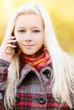 新白肤金发的蜂窝电话的谈话 免版税库存图片