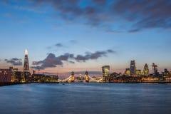新的伦敦地平线在与碎片、塔桥梁和城市的摩天大楼的晚上 库存图片