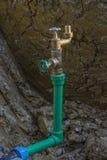 新的供水-在地面的孔与管子和水阀门 免版税图库摄影