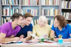 读新的信息的学生在教室 免版税库存图片