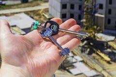从新的公寓的钥匙在背景建筑 免版税库存照片