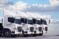 新的卡车队停放与美好的天蓝色 库存图片