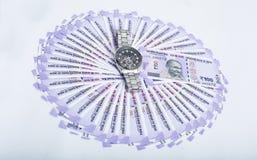 新的印度货币的图片与人手表的 图库摄影