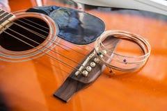 新的吉他串投入了声学吉他 免版税库存照片