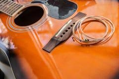 新的吉他串投入了声学吉他 免版税库存图片