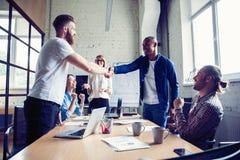 新的商务伙伴 微笑聪明的便衣的年轻现代同事握手和,当坐在时 免版税库存照片