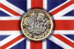 新的在英国国旗背景的1英镑硬币 库存图片