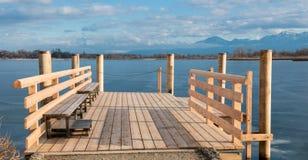 新的在冻湖Chiemsee的修造木brige 库存图片