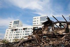 新的大厦的背景的老被破坏的木房子 免版税库存照片