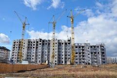 新的大厦建设中与反对蓝色多云天空的起重机 免版税库存图片