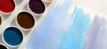 新的套水彩在纸片说谎,以蓝色冲程的形式,显示一张抽象水彩图画 骗局 库存照片