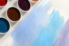 新的套水彩在纸片说谎,以蓝色冲程的形式,显示一张抽象水彩图画 骗局 库存图片