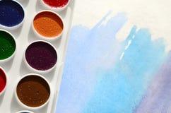 新的套水彩在纸片说谎,以蓝色冲程的形式,显示一张抽象水彩图画 骗局 图库摄影