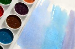 新的套水彩在纸片说谎,以蓝色冲程的形式,显示一张抽象水彩图画 骗局 免版税库存照片