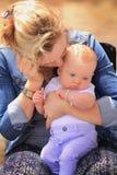 新的妈妈亲吻年轻婴孩 图库摄影