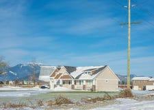 新的家庭房子有山景和前院雪的在冬天晴天 免版税库存照片
