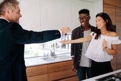新的家房地产经纪商移交的钥匙女性买家的 免版税库存照片