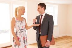 新的家房地产经纪商移交的钥匙女性买家的 免版税图库摄影