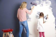 绘他们新的家的母亲和女儿 免版税库存照片
