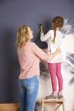 绘他们新的家的母亲和女儿 免版税图库摄影