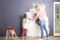 绘他们新的家的母亲和女儿 免版税库存图片
