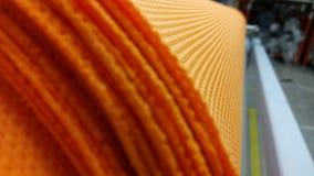 新的工业橙色卷,橙色背景 概念:材料,织品,制造,服装工厂,织品新的样品  免版税库存照片