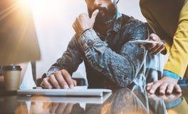 介绍新的想法企业项目的概念 谈论想法与少妇和使用桌面的有胡子的人 免版税库存图片