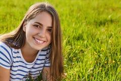 新的成人 有长的黑发、有吸引力的穿T恤杉的微笑和迷人的眼睛的一个美丽的女孩看直接地在来了 库存图片