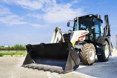 新的拖拉机在路在城市,与蓝天的一个晴天 免版税库存图片