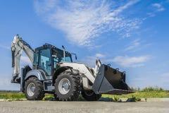 新的拖拉机在路在城市,与蓝天的一个晴天 库存照片